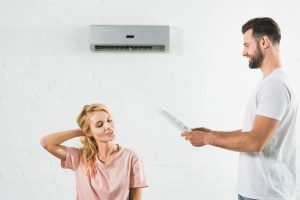 Couple,Suffering,From,Heat,Under,Air,Conditioner,At,Home